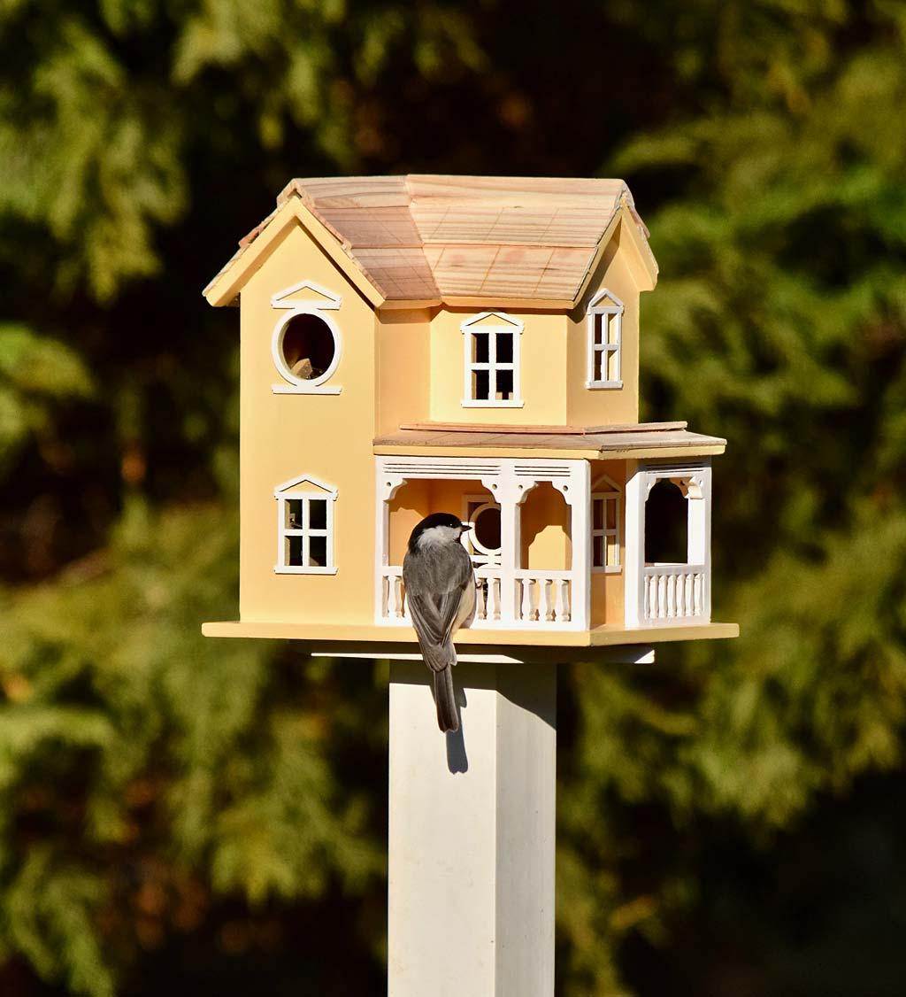 orange birdhouse with porch