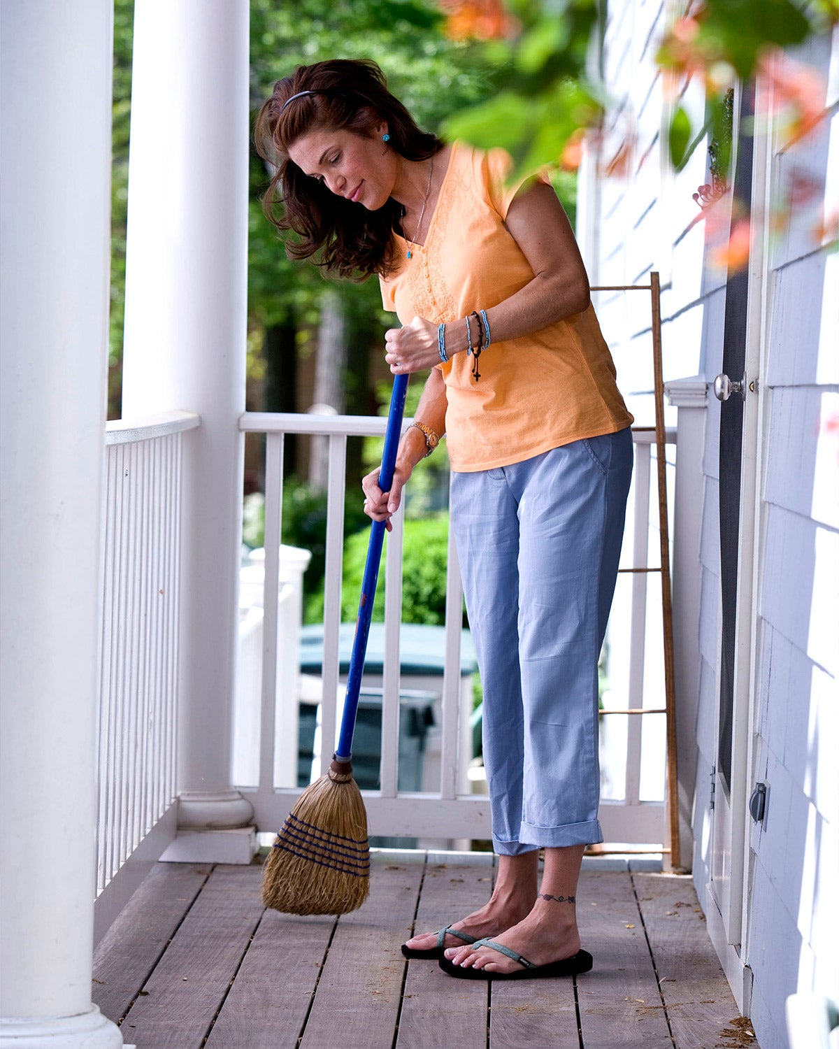 woman sweeping porch