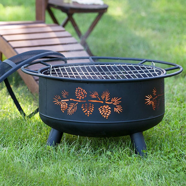 Pine Cone Wood Burning Fire Pit in Black outdoors on grass with adirondack lounge chair