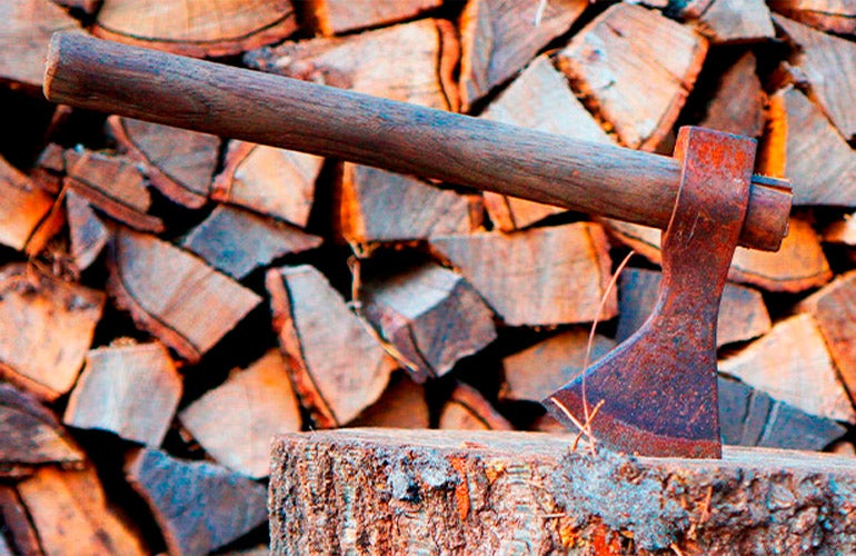 axe in stump with stack of firewood